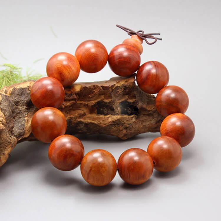 Gỗ huyết rồng thật thì màu gỗ Huyết Long đỏ vàng rất tự nhiên, có các quầng đậm và quầng nhạt màu khi tiện hạt đó là hướng màu theo thớ ngang và thớ dọc